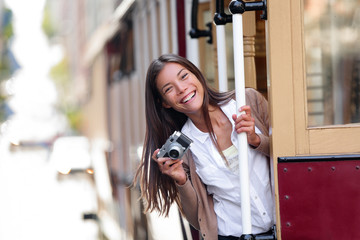 Travel lifestyle Asian woman tourist riding the famous tramway cable car system in San Francisco city, California during summer vacation. People having fun taking pictures with vintage camera.