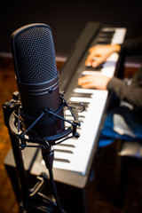 condenser microphone on musician hands playing piano background