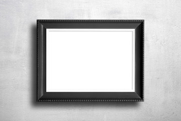 Black blank picture frame on cement wall.