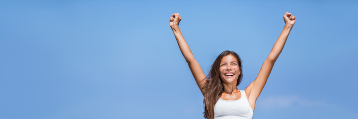 Happy success woman winner. Asian girl cheering arms up of fitness challenge achievement on summer blue background. Panorama banner crop for copyspace on sky.