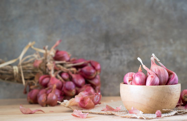 the shallots in bowl on old wooden table with old wallpaper and shallots bunch background