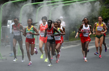 Athletes run through mist to cool down during the women's marathon at the 15th IAAF Championships in Beijing