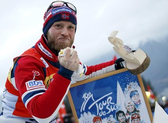 FIS Tour de Ski overall men winner Sundby celebrates as he eats a cake, after the men's cross-country skiing 9km final climb pursuit free race on the Alpe Cermis