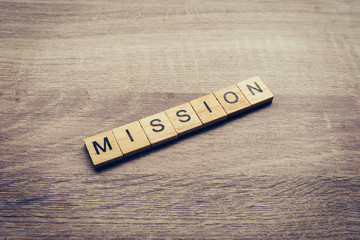 Mission word on wood table for business concept.