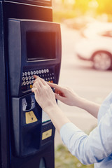 girl types the text with her hands for making out the ticket for parking machine parking and payment for travel. Concept of new technologies in road transport and toll roads.