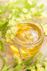 Honey in glass jars with white linden flowers on light wooden background. Shallow depth of field.