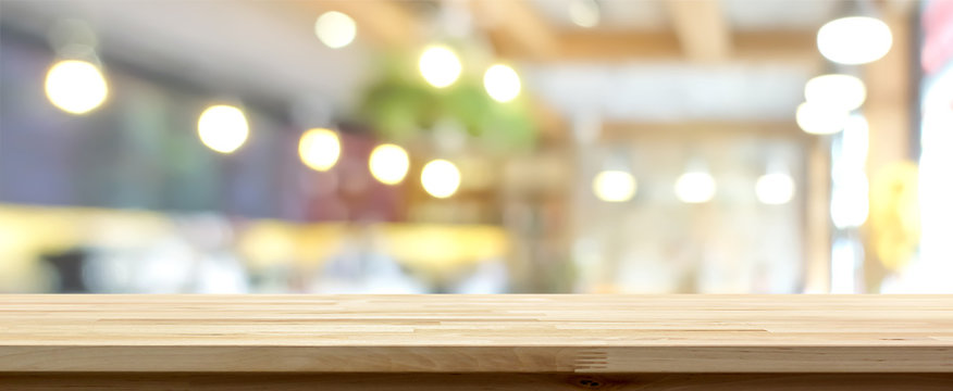 Wood table top on blur restaurant interior background, panoramic banner