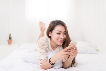 Woman Relaxing in bed and using mobile phone, relaxing in her living room