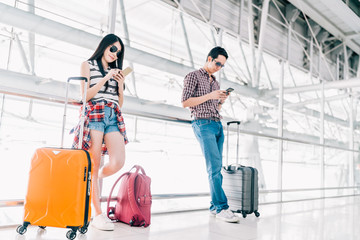 Young Asian man and woman using smartphone checking flight or online check-in at airport together, with luggage. Air travel, summer holiday, or mobile phone application technology concept