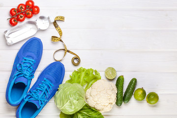Fresh healthy vegetables, sneakers on white wood background.