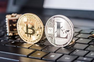 bitcoin and litecoin on black laptop keyboard