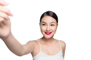 Beautiful asian woman with retro makeup with red lips taking selfie photo isolated on white background.