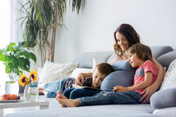 Young pregnant woman, reading a book at home to her two boys