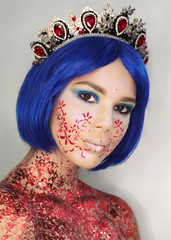 Young girl model in the art make-up like princess in a crown from fairytail looking at camera with blue hair