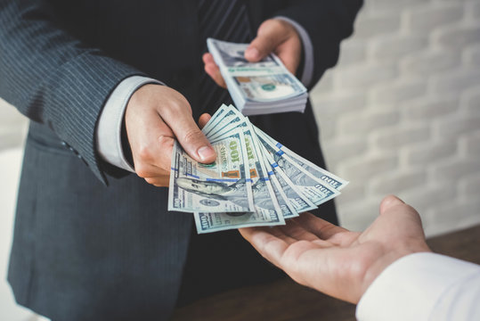 Businessman giving or paying money to a man