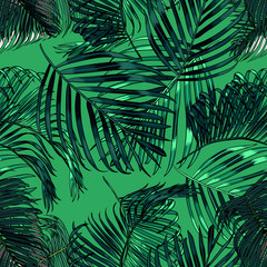 Palm leaves silhouette on the green background. seamless pattern with tropical plants.