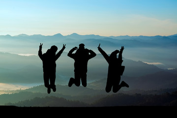 Silhouettes of friends on mountain peak. Sport and active life concept