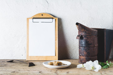 Flowers, smoker and tools on a wooden table against the background of a light wall. Concept of an apiary