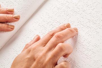 Finger read braille alphabet in white paper.