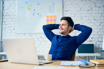 Satisfied young man in office looking away