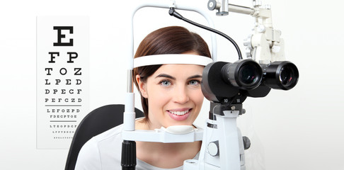 smile woman doing eyesight measurement with slit lamp and visual test chart on white