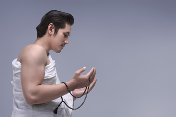 Religious asian muslim man in ihram praying with prayer beads