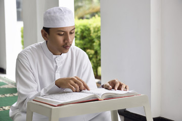 Religion asian muslim man with cap reading holy book Koran
