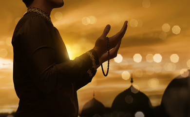 Muslim man raising hand and praying with prayer beads