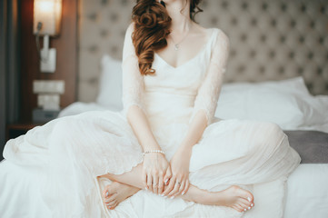 wedding Happy beautiful brunette bride in luxurious wedding dress sitting on bed waiting for groom