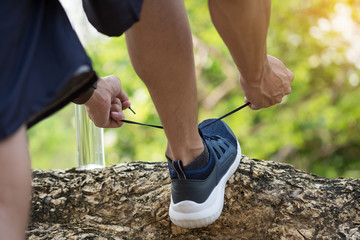 Cropped shot of young man runner tightening running shoe laces, getting ready for jogging exercise outdoors. Male jogger lacing his sneakers standing on forest path before morning run