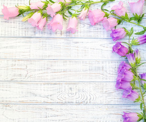 Beautiful floral frame with pink and purple bell flowers over wood, flat lay