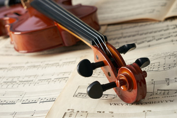 Close-up photo of vintage violin with bow and musical notes. Cello or fiddle and fiddlestick on...