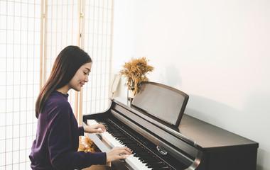 Young pretty beautiful Asian girl sitting at piano