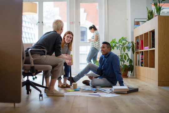 Colleagues discussing ideas with paperwork on office floor