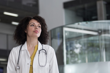 Thoughtful female doctor standing in hospital