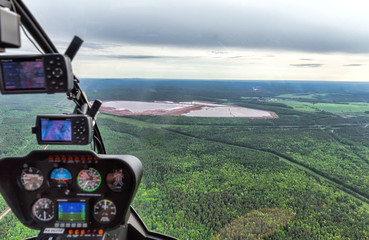 The dashboard panel in a helicopter cockpit. Northern landscape. Endless forests and swamp. Airview