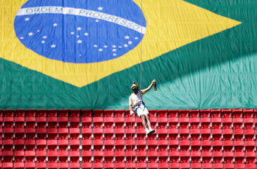 Brazilian firefighter Haudson Alves abseils with the Olympic flame as he attends the Olympic Flame torch relay at Mane Garrincha stadium in Brasilia