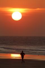 A man runs on the beach during sunset in Calais