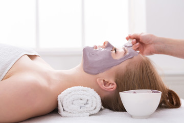 Woman gets face mask by beautician at spa