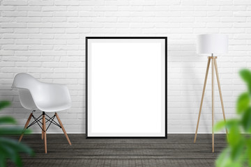 Empty picture frame leaned on brick wall. Chair and lamp beside.