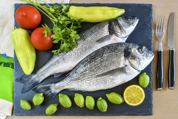 Two ready to cook raw fish with lemon and tomatoes on stone slate board.