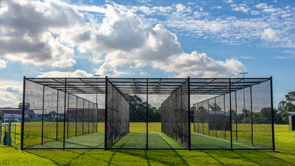 A row of cricket pratice nets on green grass and with a blue sky in Melbourne, Victoria, Australia