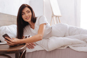 Young brunette lying in bed with smartphone