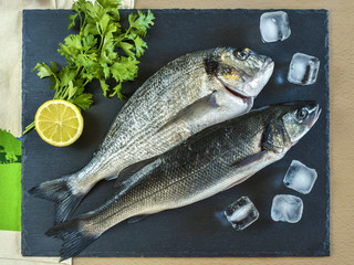 Two ready to cook raw fish with lemon on stone slate board.