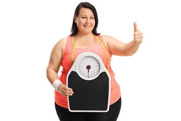 Overweight woman holding weight scale and making thumb up sign