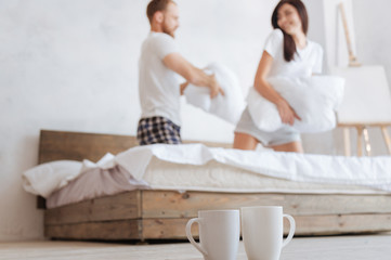 Happy couple having pillow fight in bed