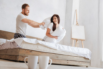 Playful couple having fight with pillows