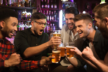 Happy male friends clinking with beer mugs in pub Wall mural