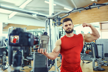 Vlogger sportsman makes a video in the gym.
