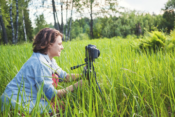 Young beautiful woman is photographing nature on camera with a tripod